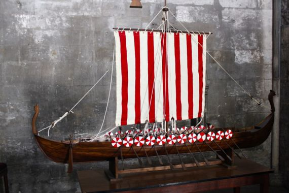 A viking ship has a single square mast and the statue of a dragon at the helm.